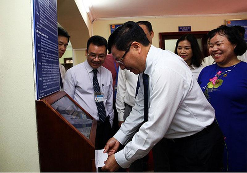 Phó Thủ tướng Phạm Bình Minh kiểm tra hệ thống lấy số tự động. Ảnh: VGP/Hải Minh
