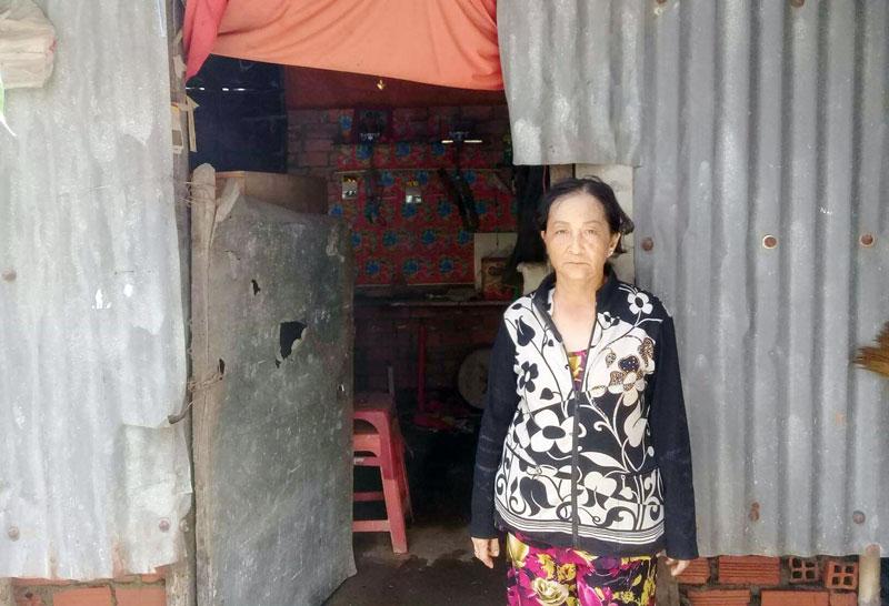 Bà Nguyễn Thị Cẩm Vân bên mái nhà che bằng vật liệu xin của người khác. Ảnh: H.Trâm