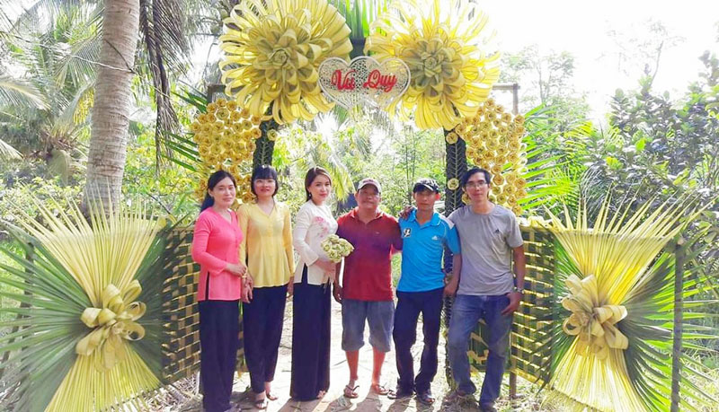 Câu lạc bộ thắt lá dừa Bến Tre chụp hình lưu niệm với cổng cưới vừa hoàn thành.