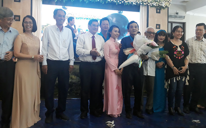 Các đại biểu tặng hoa chúc mừng họa sĩ Đoàn Việt Tiến.