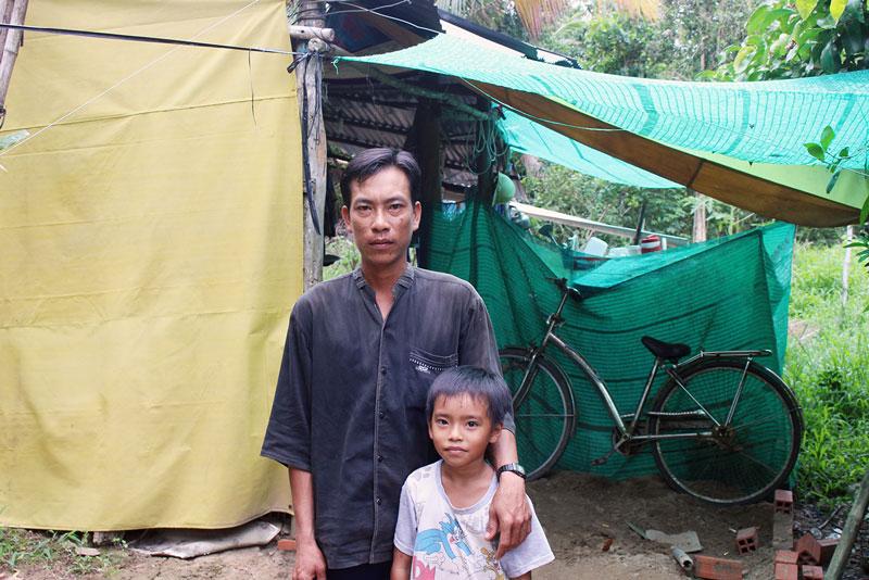 Anh Phong cùng con trai bên mái chòi dùng để che nắng, trú mưa. Ảnh: PV