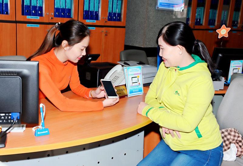 Nhân viên ngân hàng hướng dẫn khách hàng sử dụng dịch vụ thanh toán qua điện thoại thông minh. Ảnh: Hồ Ngon