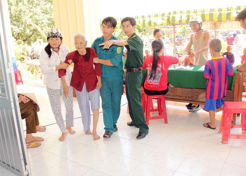 Cán bộ, đoàn viên Phòng Hậu cần hướng dẫn bà con khám bệnh trong những chuyến về nguồn khám bệnh. Ảnh: Đặng Thạch
