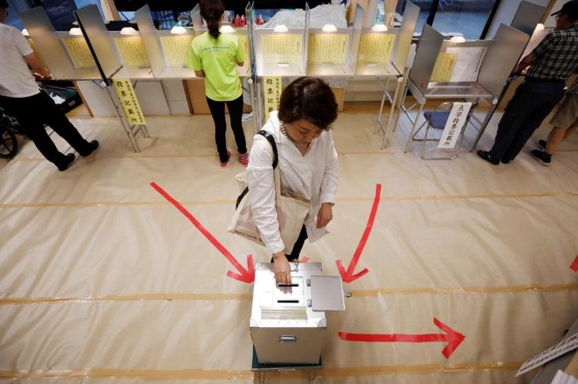 Cử tri bỏ phiếu bầu cử Thượng viện tại một trạm bỏ phiếu ở Tokyo. Ảnh: Reuters