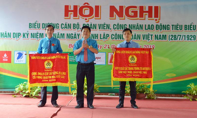 Ông Phan Song Toàn - Chủ tịch Liên đoàn lao động tỉnh trao cờ thi đua cho hai đơn vị tiêu biểu xuất sắc.