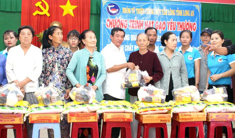 Đại diện chính quyền địa phương, Nhóm từ thiện Long An trao quà cho người dân.