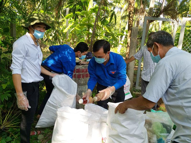 Lực lượng thu gom bao bì thuốc bảo vệ thực vật đã qua sử dụng tại vườn ông Nguyễn Văn Thật, ấp An Hòa, xã An Hiệp, huyện Châu Thành.
