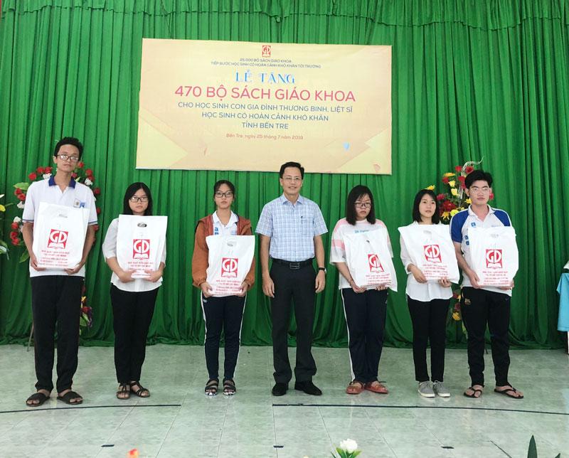 Ông Nguyễn Thành Anh trao bộ sách giáo khoa cho học sinh.