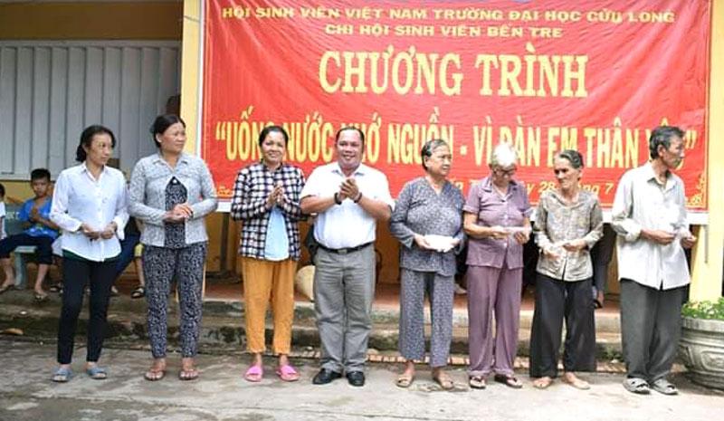 Đại diện Trường Đại học Cửu Long tặng quà cho các gia đình chính sách.