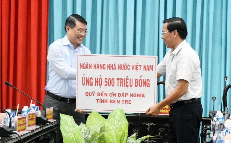 Thống đốc Ngân hàng Nhà nước Việt Nam Lê Minh Hưng trao 500 triệu đồng ủng hộ Quỹ đền ơn đáp nghĩa cho Phó bí thư Thường trực Tỉnh ủy Phan Văn Mãi.