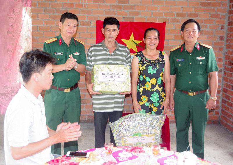 Đại tá Võ Thanh Sơn - Chính ủy Trường Quân sự tỉnh tặng quà cho gia đình chính nhân ngày trao nhà tình thương.