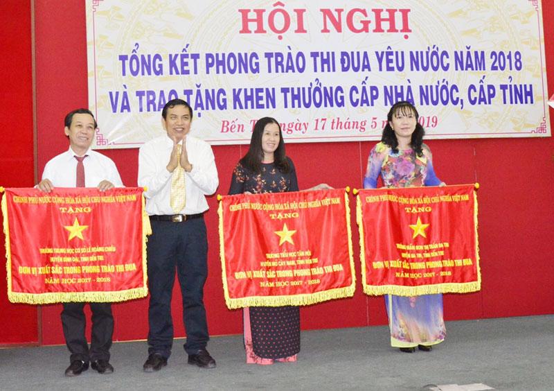 Chủ tịch UBND tỉnh Cao Văn Trọng (thứ hai, trái sang) trao cờ thi đua của Chính phủ cho Trường Tiểu học Tân Hội (thứ hai, phải sang). Ảnh: CTV