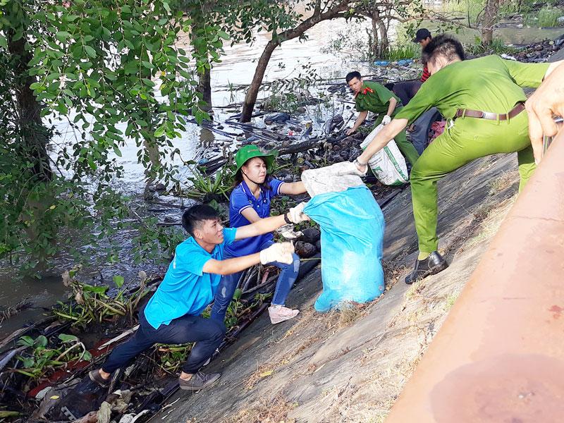 Các bạn trẻ nhiệt tình dọn rác, bảo vệ môi trường. Ảnh: K.M