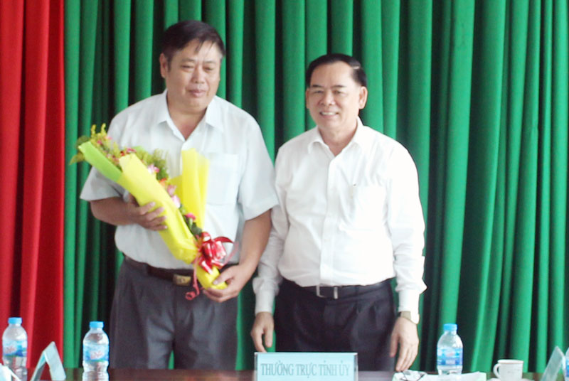Phó bí thư Thường trực Tỉnh ủy Trần Ngọc Tam tặng hoa cho ông Lao Văn Trường.  Ảnh: T.Lập