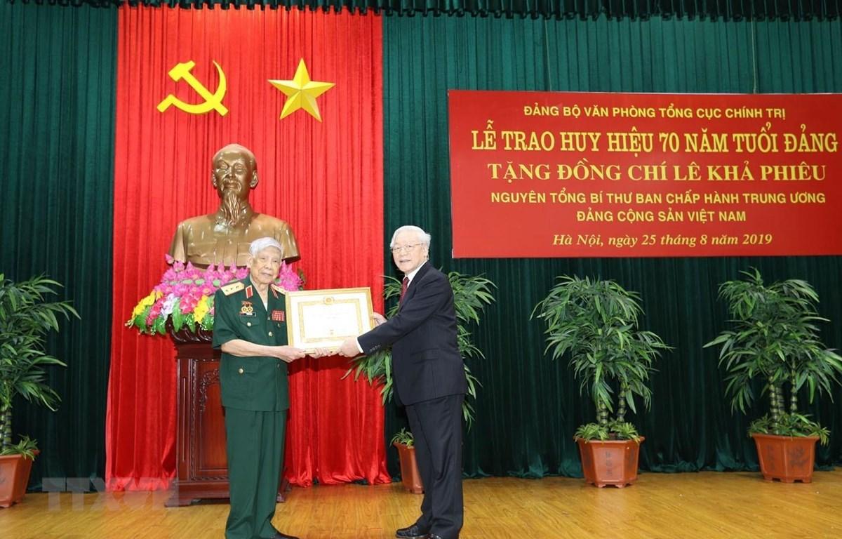 Tổng Bí thư, Chủ tịch nước Nguyễn Phú Trọng, Bí thư Quân ủy Trung ương trao Huy hiệu 70 năm tuổi Đảng tặng nguyên Tổng Bí thư Lê Khả Phiêu. Ảnh: Trí Dũng/TTXVN