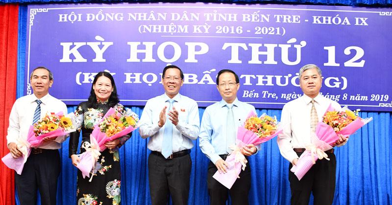 Bí thư Tỉnh ủy, Chủ tịch HĐND tỉnh Phan Văn Mãi trao hoa chúc mừng các đồng chí được bầu vào UBND, HĐND tỉnh.