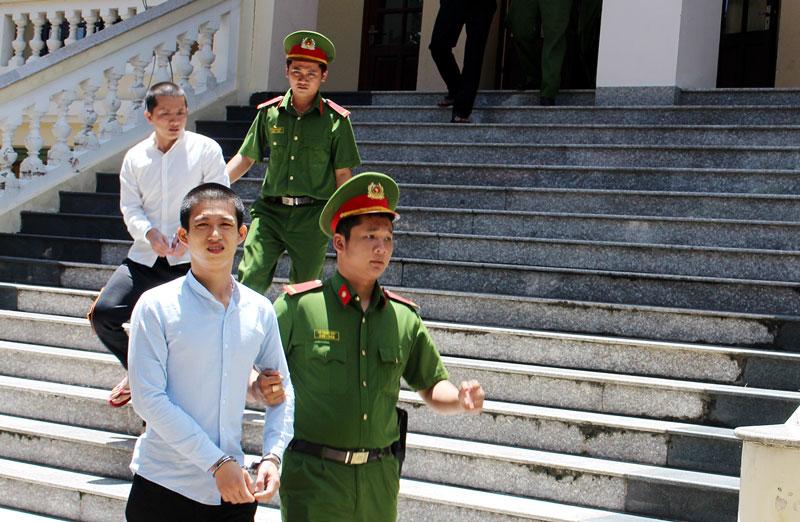 Lực lượng Cảnh sát bảo vệ áp giải các bị cáo lên xe về nhà giam, bị cáo Ngọc (đi trước).