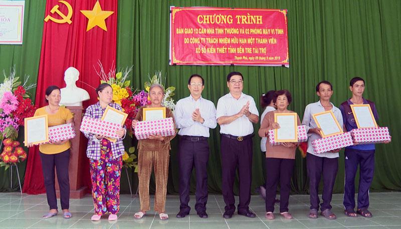Bí thư Huyện ủy Nguyễn Trúc Sơn và đơn vị tài trợ trao quyết định bàn giao nhà và tặng quà cho các hộ gia đình.