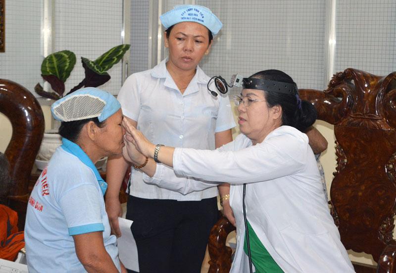 Bác sĩ đang kiểm tra mắt cho các chị em nữ công nhân.