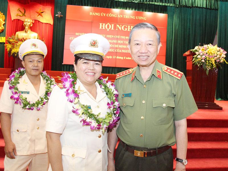 Trung tá Nguyễn Thị Thu Thủy chụp ảnh lưu niệm cùng Đại tướng Tô Lâm - Bộ trưởng Bộ Công an tại Hội nghị sơ kết 3 năm thực hiện Chỉ thị số 05-CT/TW do Đảng ủy Công an Trung ương tổ chức.  Ảnh: NVCC