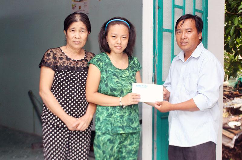 Anh Huỳnh Văn Tài - Bí thư Xã Đoàn Vĩnh Hòa trao tiền hỗ trợ của bạn đọc cho chị Ngân và người thân. Ảnh: H. Đức