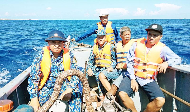 Các ngư dân được cứu sống đưa lên xuồng.