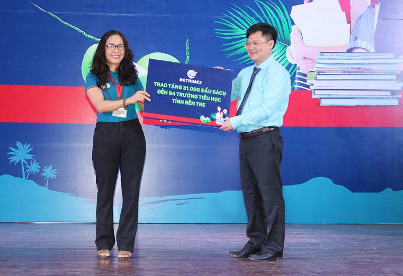 Phó chủ tịch Hội đồng quản trị Công ty Betrimex Thái Văn Chuyện trao bảng tượng trưng tặng sách cho Dự án sách hay cho học sinh tiểu học.