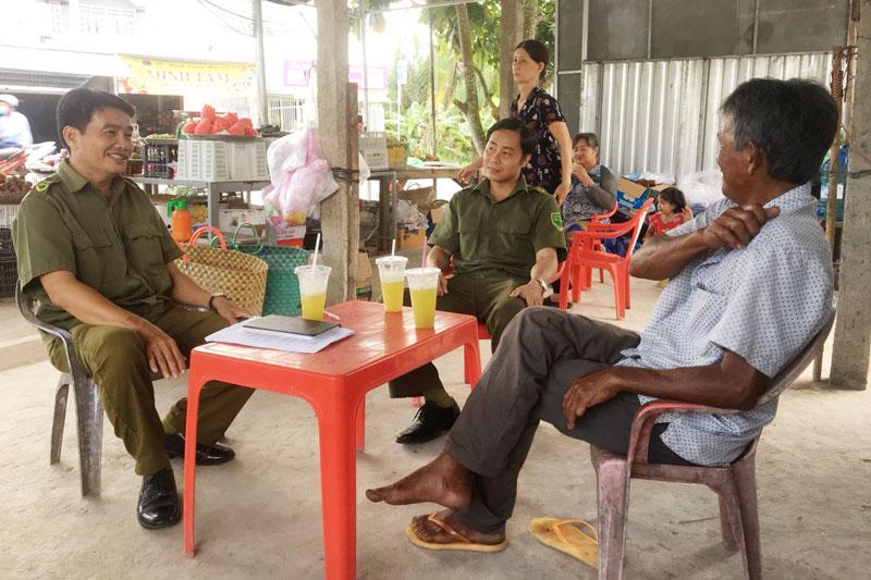 Anh Trần Văn Minh (ngồi bên trái) xuống địa bàn để nắm tình hình an ninh trật tự trong nhân dân.