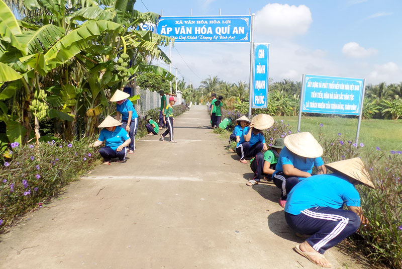 Đội thiếu niên bảo vệ môi trường cùng phụ nữ ấp dọn dẹp vệ sinh môi trường tại tuyến đường ấp Quí An.