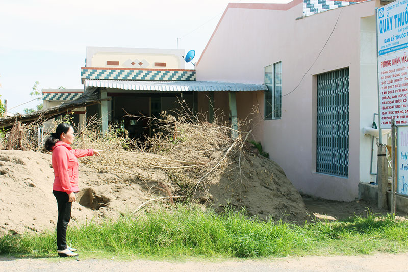 Bà N.T.Ch. đứng trước nhà đã bị bà N. đổ đống đất chắn ngang. Ảnh: PV