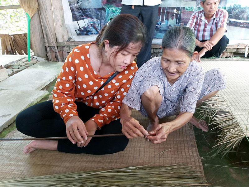 Người dân địa phương hướng dẫn cho du khách trải nghiệm một công đoạn dệt chiếu tại làng chiếu Nhơn Thạnh (TP. Bến Tre). Ảnh: T. Đồng