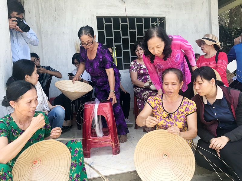 Du khách được người dân hướng dẫn đan nón lá. Ảnh: PV