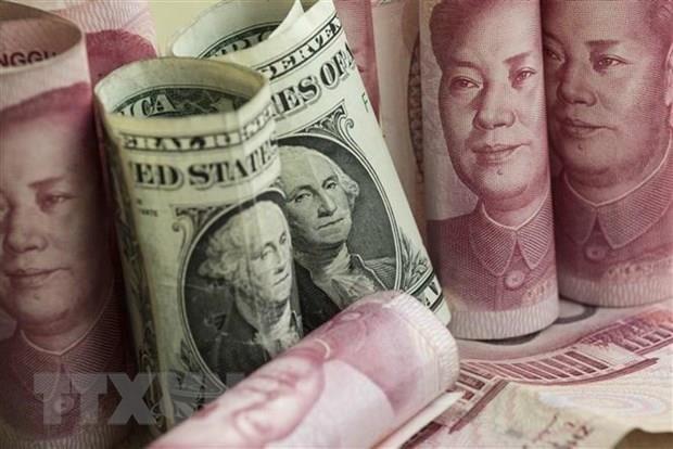 Đồng nhân dân tệ và đồng USD tại một ngân hàng ở Bắc Kinh, Trung Quốc. Ảnh: AFP/TTXVN