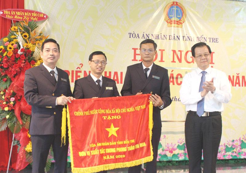 Phó Chánh án TAND tối cao Lê Hồng Quang (bìa phải) trao Cờ thi đua của Chính phủ cho đại diện lãnh đạo TAND tỉnh