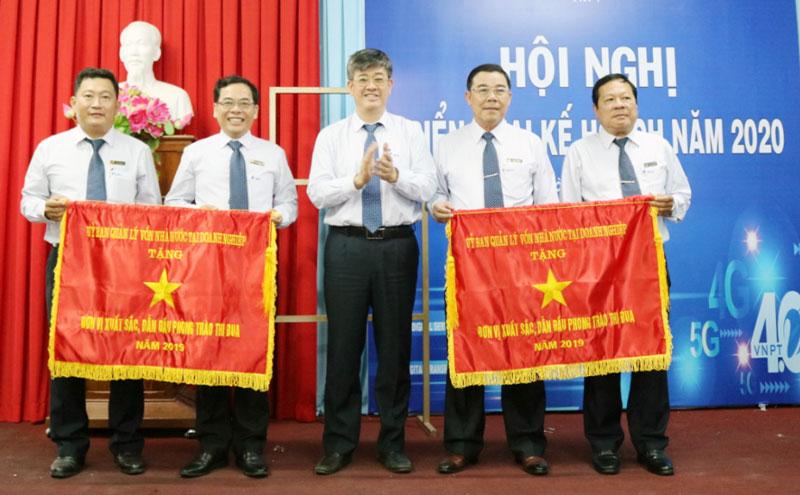 Ông Hồ Đức Thắng (đứng giữa) trao Cờ đơn vị xuất sắc dẫn đầu phong trào thi đua năm 2019 cho VNPT Bến Tre và Trung tâm kinh doanh VNPT – Bến Tre.
