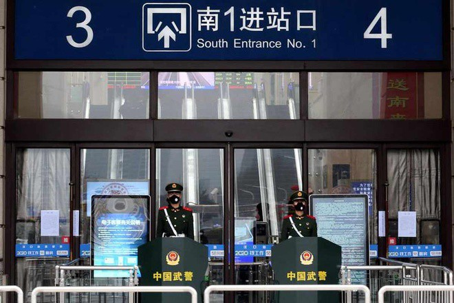 Các sĩ quan bán quân sự Trung Quốc đeo mặt nạ bảo vệ ở lối vào của nhà ga Hankou đã đóng cửa sau khi thành phố bị phong tỏa ở Vũ Hán, tỉnh Hồ Bắc, Trung Quốc, ngày 23-1-2020. Ảnh: Reuters