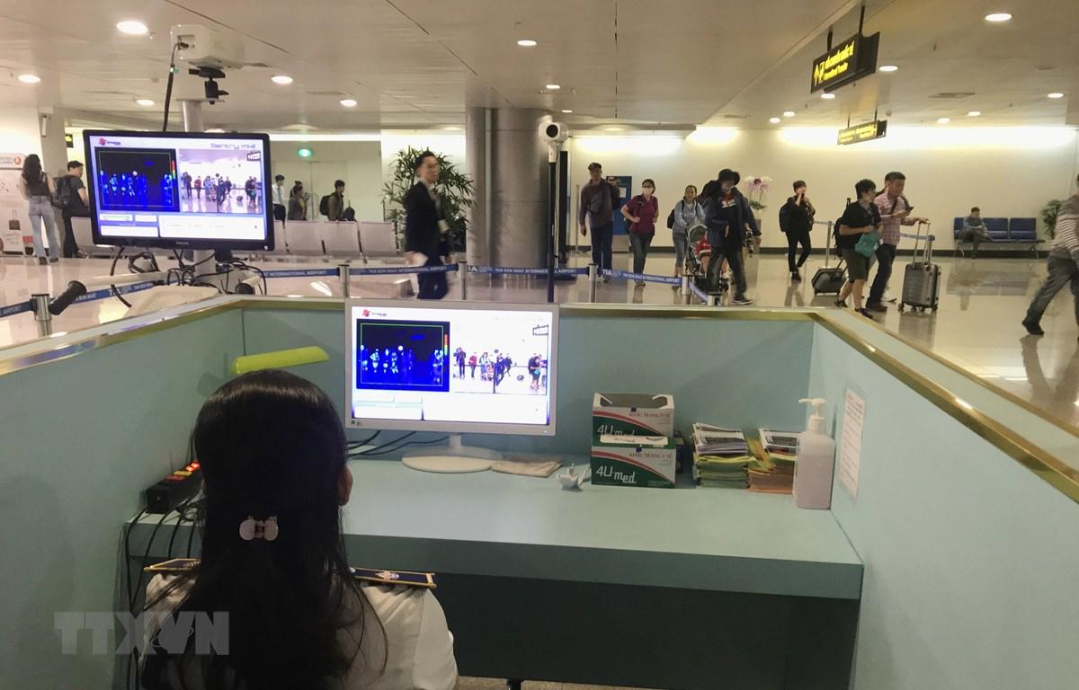Nhân viên sân bay Tân Sơn Nhất kiểm tra màn hình hiển thị máy quét thân nhiệt đối với hành khách quốc tế đến Việt Nam. Ảnh: Đinh Hằng/TTXVN