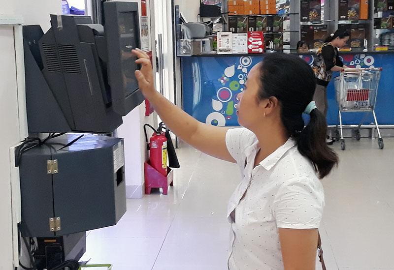 Khách hàng sử dụng mã để thanh toán không dùng tiền mặt trong mua sắm tại siêu thị.