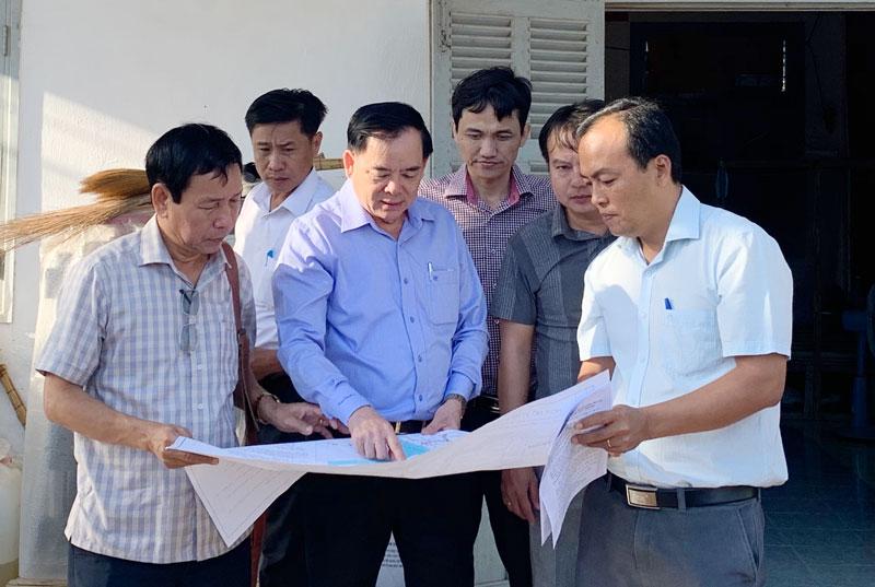 Phó bí thư Thường trực Tỉnh ủy Trần Ngọc Tam xem bản vẽ công trình xây dựng đê bao ngăn mặn kết hợp đường giao thông nối liền các huyện ven biển Bình Đại - Ba Tri - Thạnh Phú (giai đoạn 1).