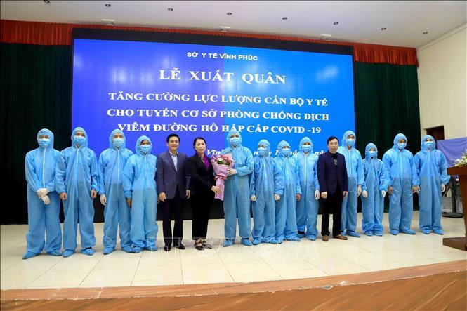Lãnh đạo tỉnh Vĩnh Phúc tặng hoa cho 13 đội trưởng của đội ngũ cán bộ y tế tham dự Lễ xuất quân. Ảnh: Hoàng Hùng/TTXVN