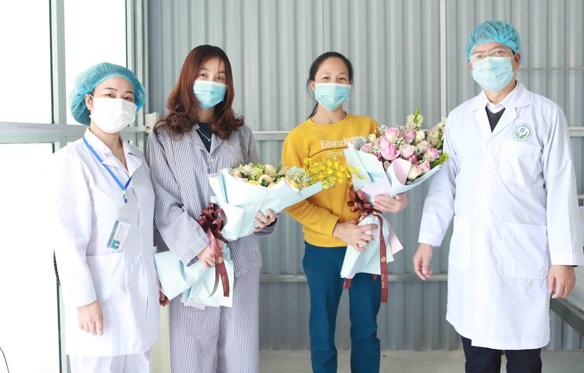 """Hai bệnh nhân nhiễm dịch COVID-19 được chữa khỏi ở bệnh viện tuyến huyện tại """"tâm dịch Bình Xuyên"""". Ảnh: Hoàng Hùng/TTXVN"""