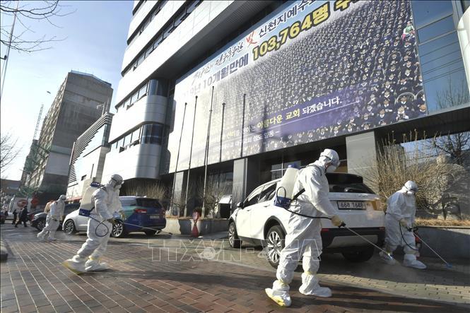 Nhân viên y tế phun thuốc khử trùng phía trước một nhà thờ của giáo phái Shincheonji ở Daegu, Hàn Quốc, nhằm ngăn chặn sự lây lan của COVID-19, ngày 19-2-2020. Ảnh: AFP/TTXVN