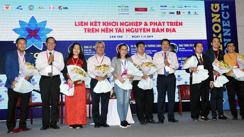Bí thư Tỉnh ủy Phan Văn Mãi, Phó chủ tịch UBND tỉnh Nguyễn Hữu Lập tặng hoa cho các chuyên gia gợi ý liên kết khởi nghiệp và phát triển trên nền tài nguyên bản địa.
