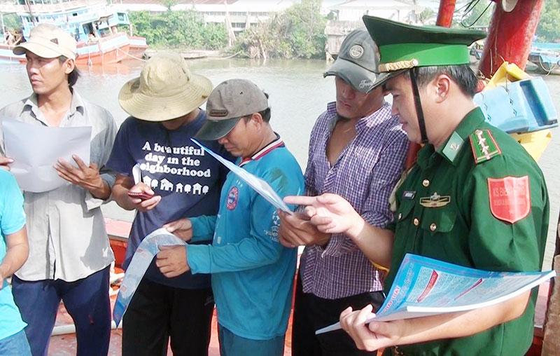 Cán bộ Trạm Kiểm soát biên phòng Bình Thắng (Bình Đại) phát tờ rơi tuyên truyền pháp luật cho ngư dân. Ảnh: Biên Cương