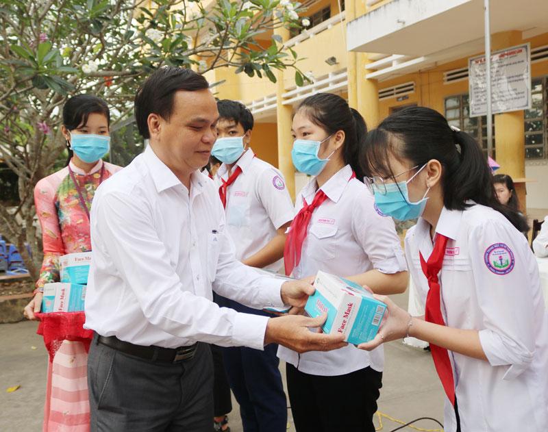 Học sinh nhận khẩu trang y tế và nước rửa tay.