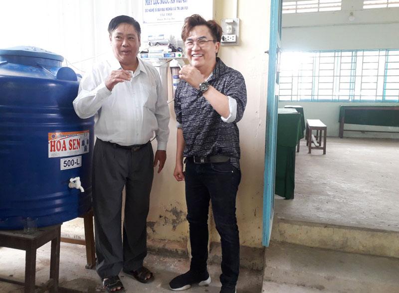 Ông Lao Văn Trường - Chủ tịch Hội Nông dân tỉnh và nghệ sĩ Bùi Đại Nghĩa thực hiện nghi thức Bàn giao máy lọc nước.