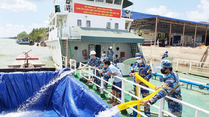Cán bộ, chiến sỹ Tàu 937 bơm nước ngọt xuống ghe cho bà con xã Tân Trung, Mỏ Cày Nam.