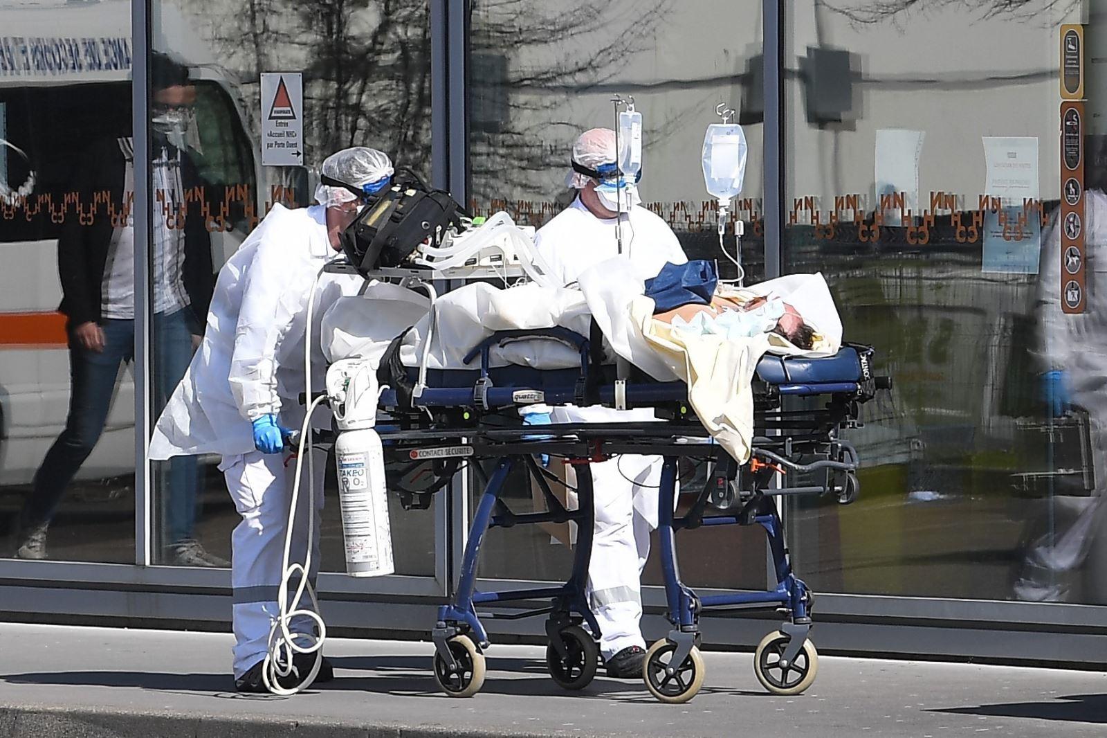 Nhân viên y tế chuyển bệnh nhân nhiễm COVID-19 tới bệnh viện ở Strasbourg, Pháp, ngày 16-3-2020. Ảnh: AFP/ TTXVN