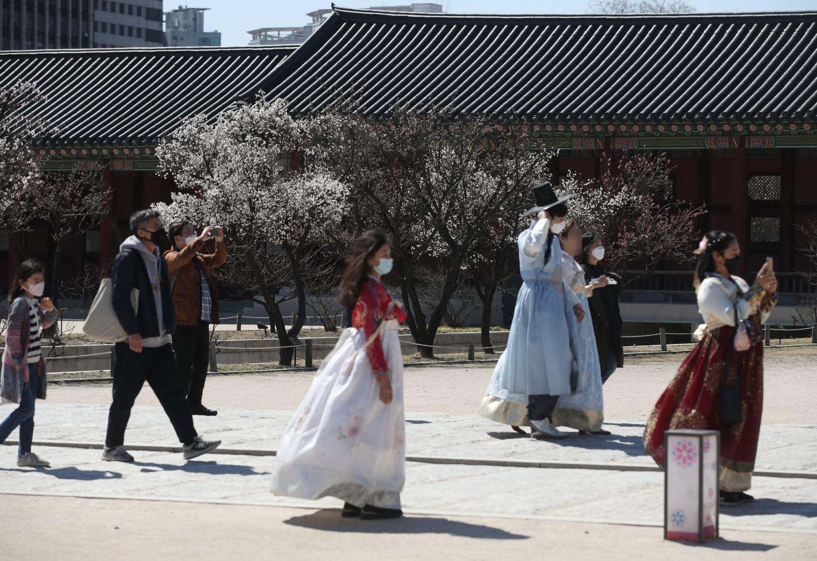 Du khách đeo khẩu trang để phòng tránh lây nhiễm COVID-19 tại Seoul, Hàn Quốc, ngày 22-3-2020. Ảnh: THX/ TTXVN