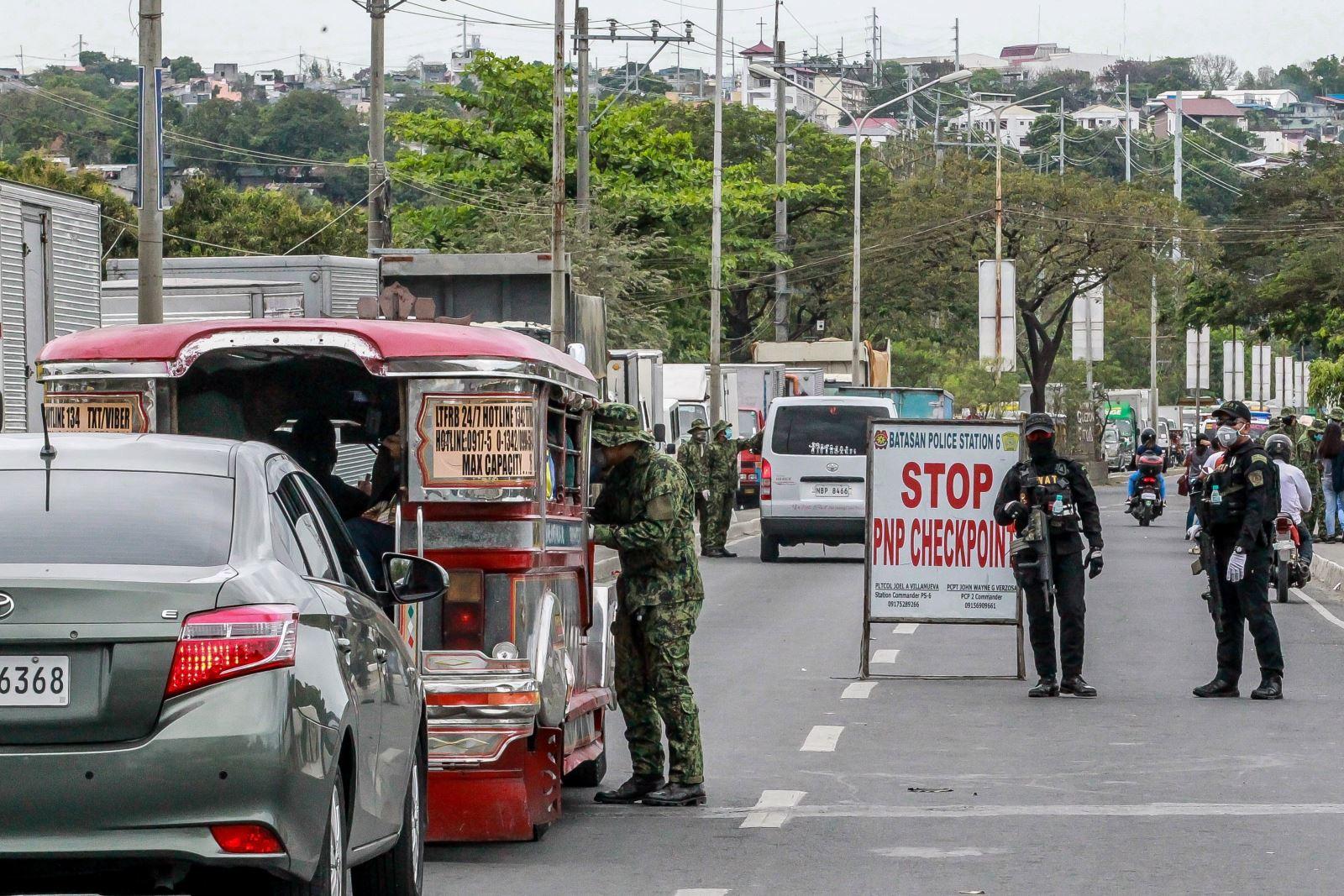 Cảnh sát kiểm tra thân nhiệt của người dân tại một điểm kiểm soát ở Quezon, Philippines ngày 16-3-2020, nhằm ngăn chặn sự lây lan của COVID-19. Ảnh: THX/ TTXVN